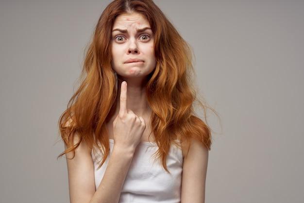 Femme avec l'acné des cheveux lâches sur son visage l'acné faisant des gestes avec ses mains. photo de haute qualité