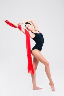 Femme acrobate en costume de gymnaste posant isolé sur un mur blanc