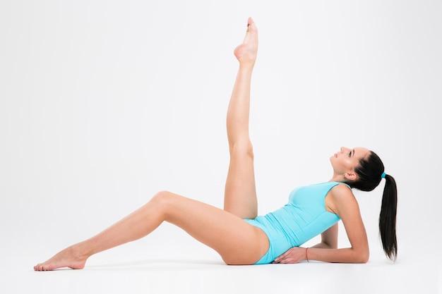 Femme acrobate qui s'étend sur le sol isolé sur un mur blanc