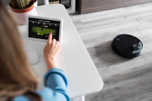 Femme activant le robot nettoyeur
