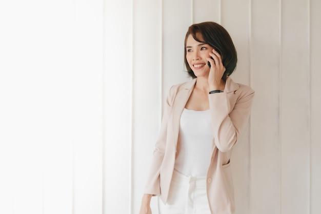 Une femme active asiatique heureuse a une conversation avec un smartphone