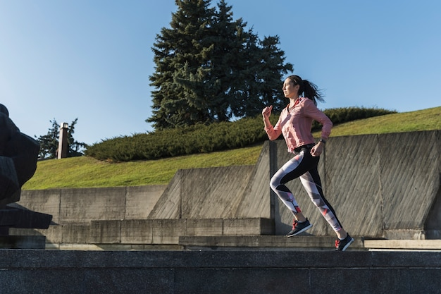 Femme active plein écran qui court en plein air