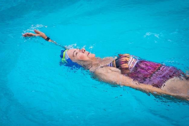 Femme active senior dans une activité saine nageant dans la piscine extérieure turquoise