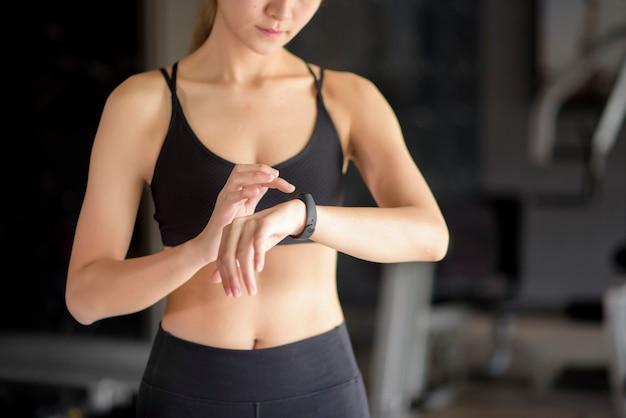 Une femme active utilise une montre intelligente dans une salle de fitness. concept de remise en forme et de technologie.