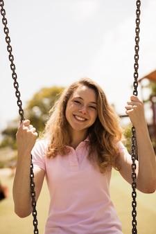 Femme adolescente joyeuse sur les balançoires