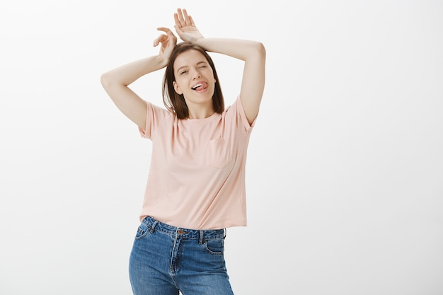 Femme adolescente mignonne insouciante montrant le geste des oreilles de lapin et la langue, clignant des yeux idiot