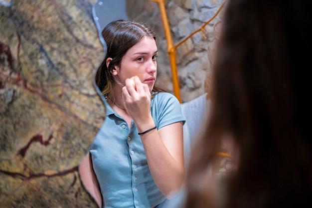 Femme adolescente se maquiller dans la salle de bain.