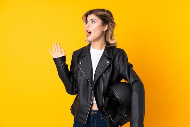 Femme adolescente tenant un casque de moto isolé sur un mur jaune avec une expression faciale surprise