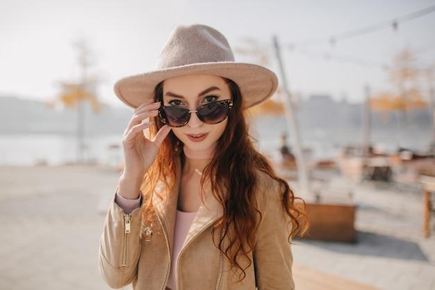 Femme adorable aux cheveux roux ondulés touchant ses lunettes de soleil