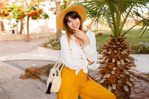 Femme adorable en chapeau de paille et chemisier blanc posant dans un hôtel tropical pendant les vacances.
