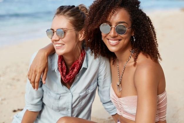 Une femme adorable avec une coiffure afro embrasse sa partenaire féminine, commence les lesbiennes, apprécie la convivialité et l'atmosphère calme au bord de la mer, admire la vue, a des regards heureux. les gens, le style de vie, les loisirs