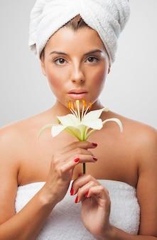 Femme adorable dans une serviette avec une fleur de lys