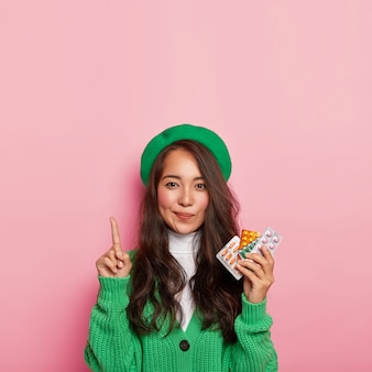 Une femme adorable pointe ci-dessus, tient des analgésiques, a des problèmes de santé, se dirige vers un magasin de pharmacie, vêtue d'une tenue à la mode verte