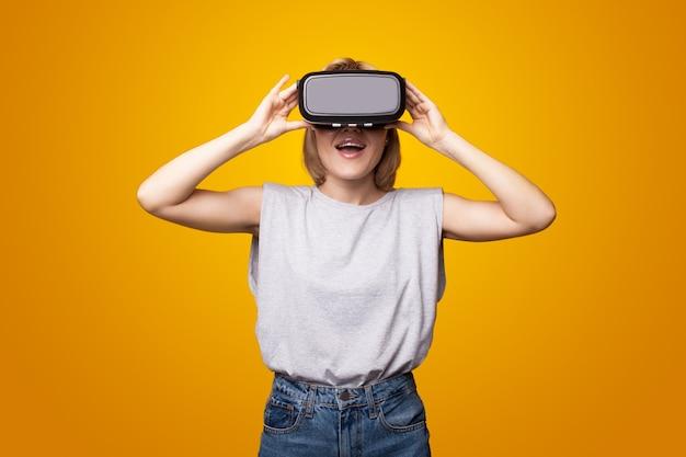 Une femme adorable sourit en utilisant un casque de réalité virtuelle et se fait surprendre sur un studio jaune...