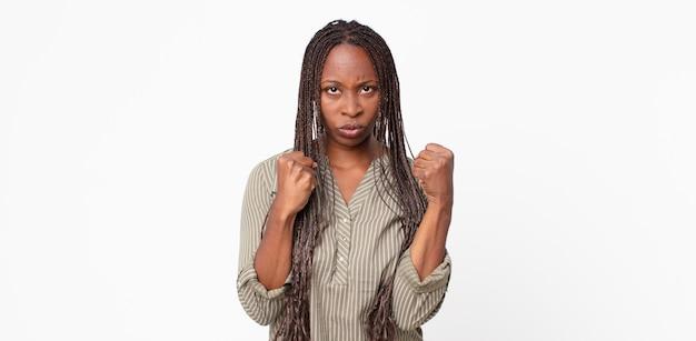 Femme adulte afro noire à l'air confiante, en colère, forte et agressive, avec les poings prêts à se battre en position de boxe
