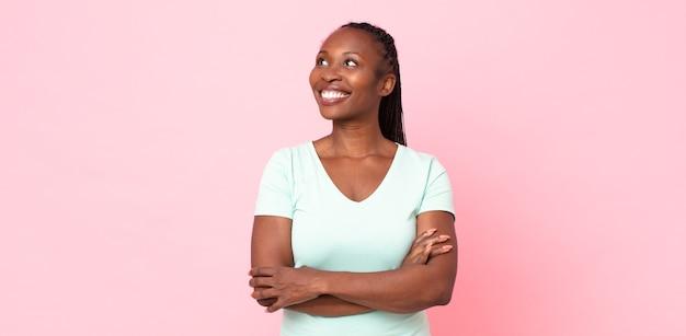 Femme adulte afro noire se sentant heureuse, fière et pleine d'espoir, se demandant ou pensant, levant les yeux pour copier l'espace avec les bras croisés
