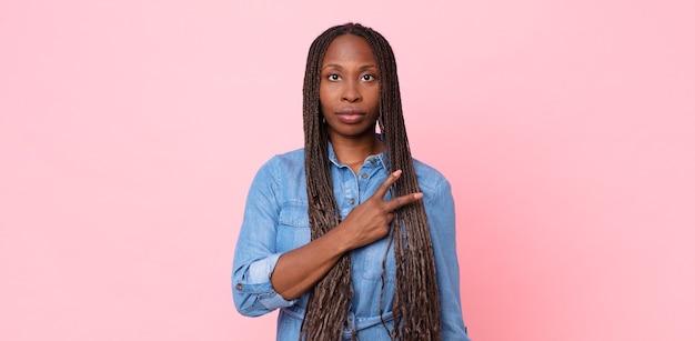 Femme adulte afro noire se sentant heureuse, positive et réussie, avec la main en forme de v sur la poitrine, montrant la victoire ou la paix
