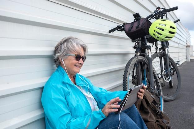 Une femme adulte âgée et séduisante arrête de faire du vélo électrique et s'assoit contre un mur blanc en regardant un ordinateur portable. une personne aux cheveux gris et aux vêtements décontractés