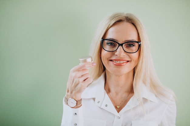 Femme adulte à l'aide d'une crème anti-âge
