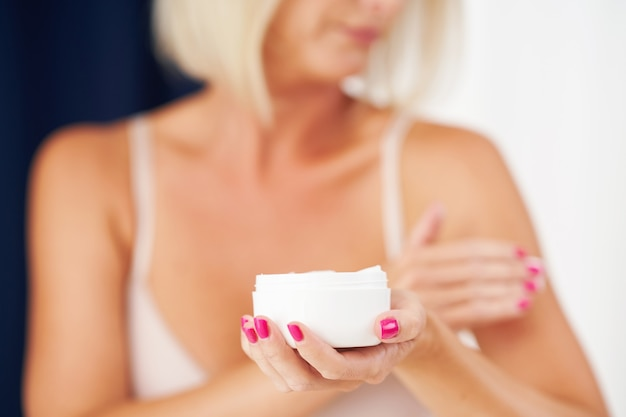 Femme adulte appliquant une crème hydratante pour le corps à la maison