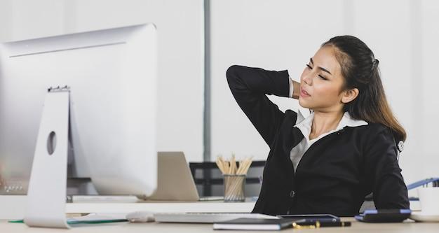 Femme adulte asiatique est des gens de bureau assis au bureau au travail de bureau, elle essaie de travailler dur, la douleur de son cou ressemble au syndrome du bureau.