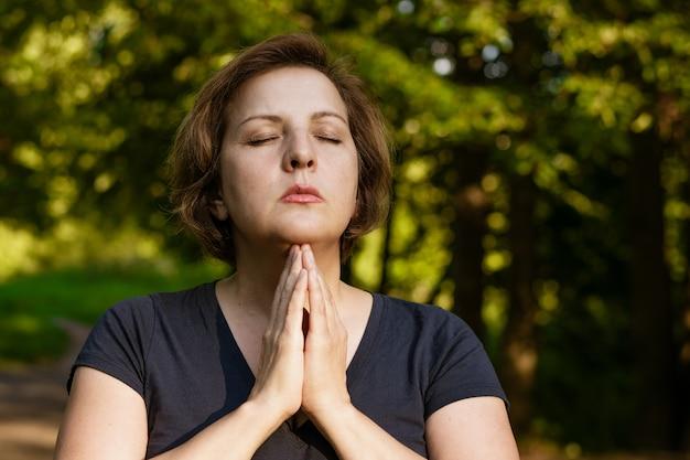 Femme adulte aux cheveux courts médite avec les paumes pliées dans le parc avec les yeux fermés dans les rayons du soleil gaggle en été