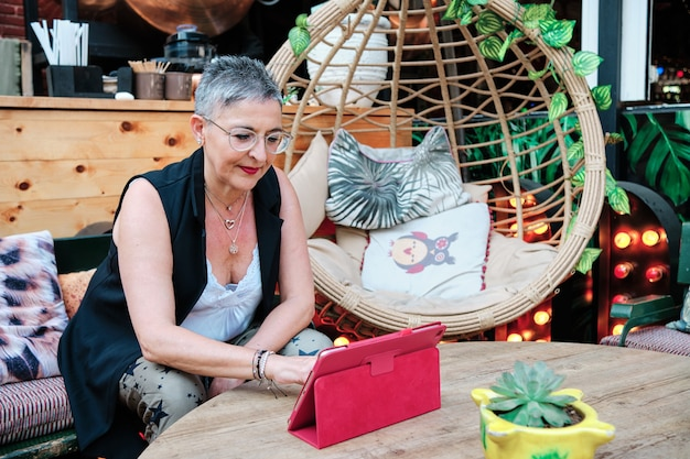 Femme adulte aux cheveux gris argenté utilisant une tablette - nouveau concept technologique
