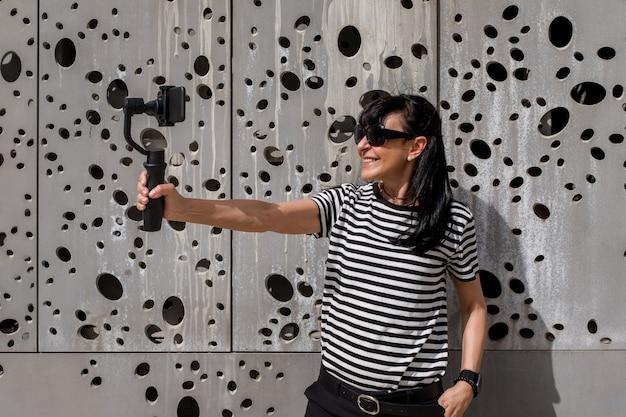 Femme adulte aux cheveux longs tournage avec téléphone portable sur un stabilisateur dans la rue par une journée ensoleillée
