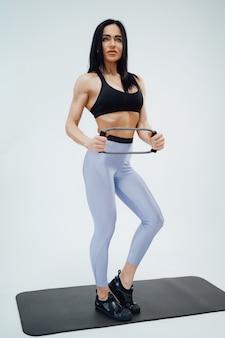 Une femme adulte aux cheveux noirs en vêtements de sport posant sur fond blanc fait de l'exercice physique avec des bandes de résistance en caoutchouc.