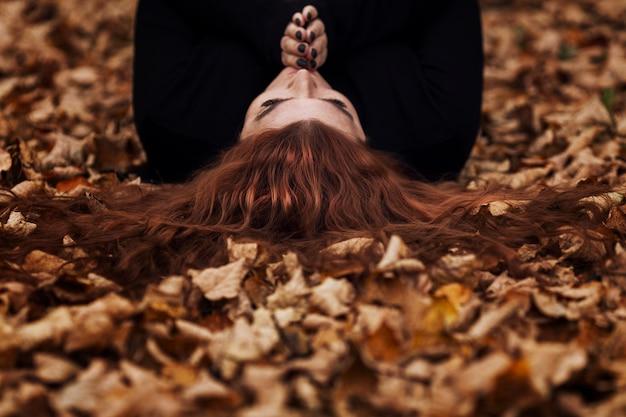 Une femme adulte aux longs cheveux roux se trouve sur le sol dans le feuillage d'automne.