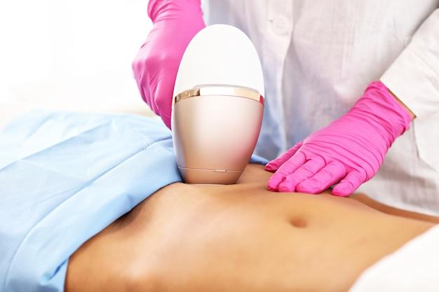 Femme adulte ayant l'épilation au laser dans un salon de beauté professionnel