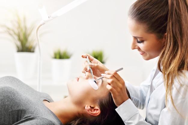 Femme adulte ayant une extension de cils dans un salon de beauté professionnel