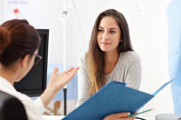 Femme adulte ayant une visite au bureau du médecin féminin