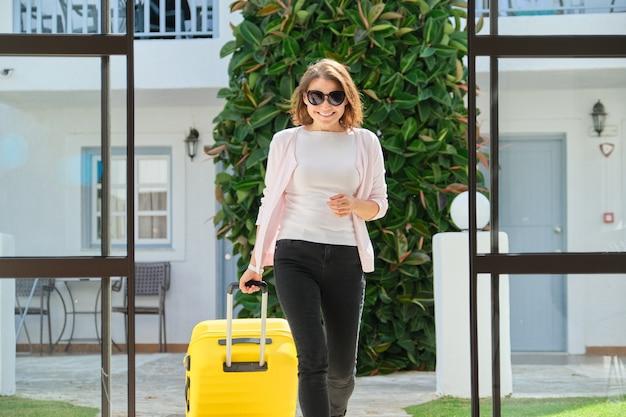 Femme adulte avec des bagages avec valise allant dans le hall de l'hôtel, femme voyageant avec voyage d'affaires
