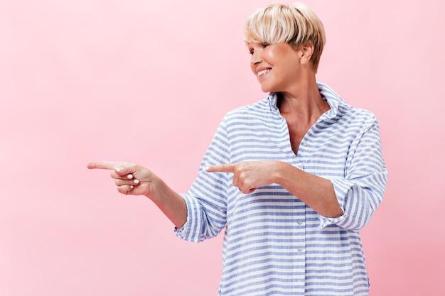 Femme adulte en chemise à carreaux pointant vers la place pour le texte