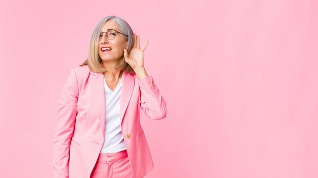 Femme adulte en costume rose essayant d'écouter les potins ou d'entendre un secret