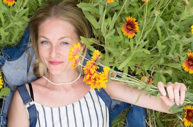 Une femme adulte dans un champ de blé a l'air jeune et naturelle