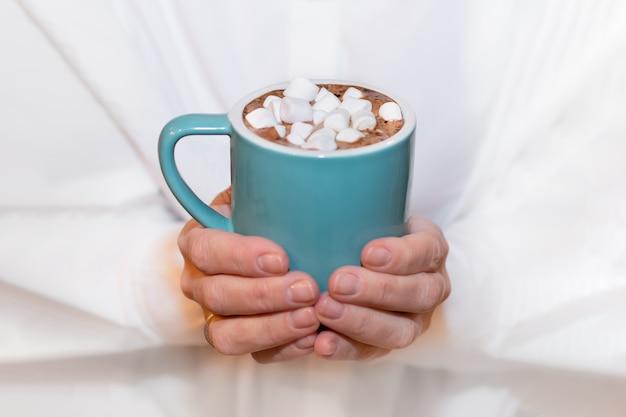 Une femme adulte dans une chemise blanche tient une tasse bleue de cacao avec des guimauves dans ses mains.