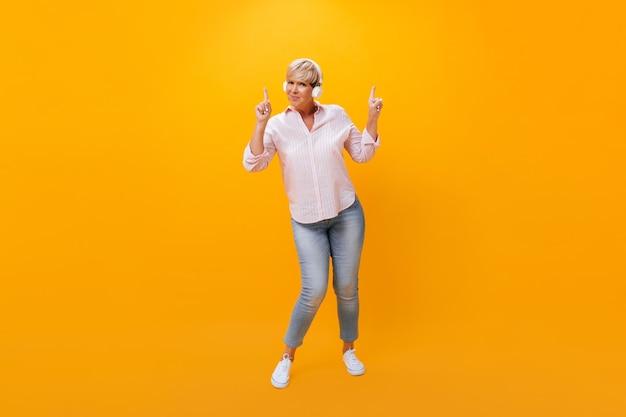 Femme adulte dans les écouteurs pointant vers le haut sur fond orange