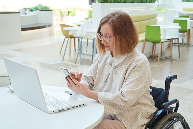 Une femme adulte dans un fauteuil roulant travaille sur un ordinateur portable