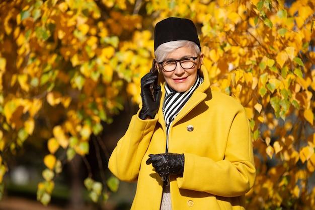 Femme adulte dans des verres dans le parc à l'automne avec un téléphone mobile