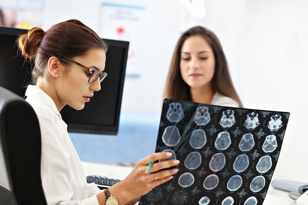 Femme adulte discutant des résultats des rayons x lors d'une visite au cabinet d'une femme médecin