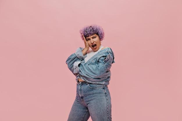 Une femme adulte émotionnelle aux cheveux violets courts bouclés est surprise sur le rose. dame moderne en vêtements de jeans.