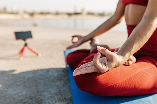 Femme adulte enregistrant un didacticiel vidéo de cours de yoga sur téléphone portable - concept de cours de fitness virtuel de yoga