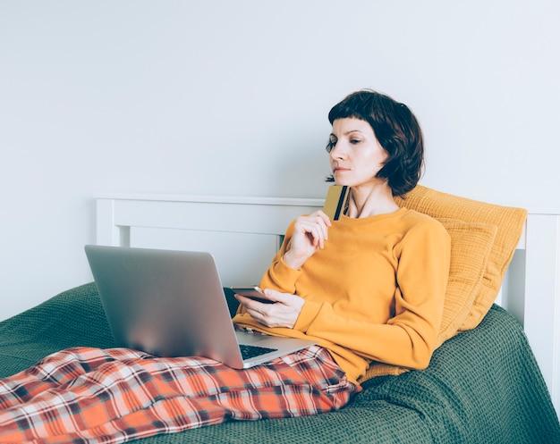 Une femme adulte essayant de décider quoi acheter en ligne