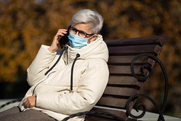 Femme adulte est assise sur un banc à parler au téléphone