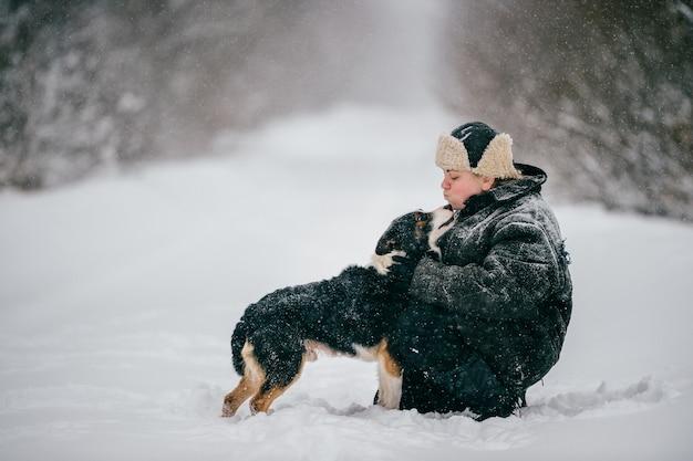 Femme adulte étreignant adorable chien sur la route d'hiver à l'extérieur.