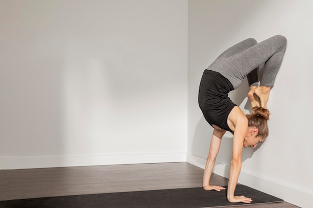 Femme adulte, faire du yoga à la maison
