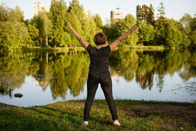Femme adulte, faire des exercices au bord du lac dans le parc un jour d'été