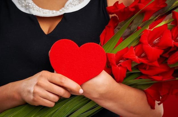 Femme adulte avec des fleurs et coeur rouge sur fond rouge
